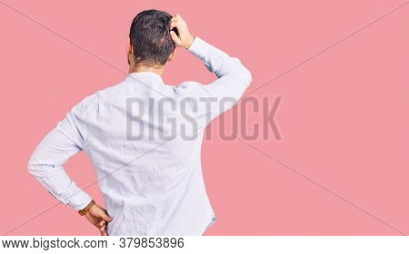 Handsome young man with bear wearing elegant business shirt and glasses backwards thinking about doubt with hand on head
