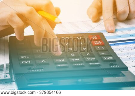 Business Mans Hands Count On A Calculator. Office Desk With Charts And Financial Documents. Concept