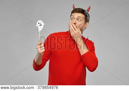 holiday, photo booth and people concept - man in halloween costume of devil with party accessory over grey background