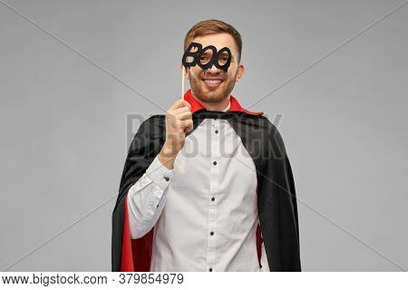 holiday, photo booth and people concept - happy smiling man in halloween costume of vampire and dracula cape with party accessory over grey background