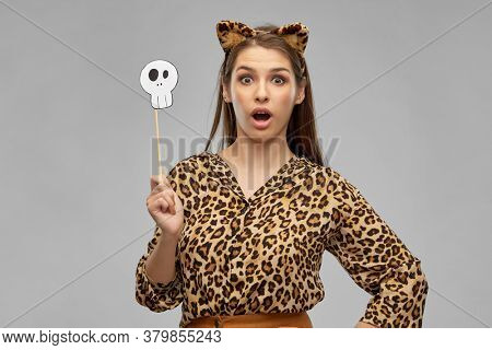 holiday, photo booth and people concept - surprised woman in halloween costume of leopard with ears and scull party accessory over grey background