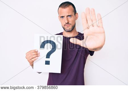 Young handsome man with tattoo holding question mark with open hand doing stop sign with serious and confident expression, defense gesture