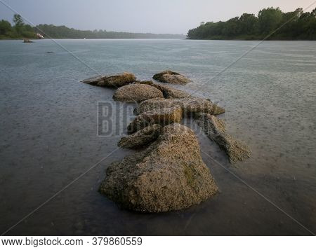 A Beautiful Scenic View Of Rocks Or Boulders In The Sava River Against Dramatic Ominous Storm Clouds