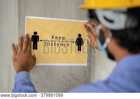 Worker Pasting Keep 6 Feet Distance On Wall At Work Place Or Construction Site Due To Coronavirus Or
