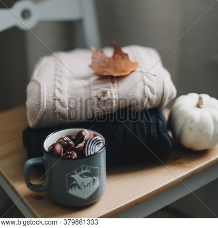 Pile Of Knitted Winter, Autumn Clothes On Wooden Background, Sweaters, Knitwear, Leaf. Cozy Autumn,