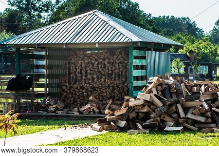 Modern Farm With A Beautiful Lawn And A Firewood Shed. The Logs Lie Neatly Under The Canopy. Near A