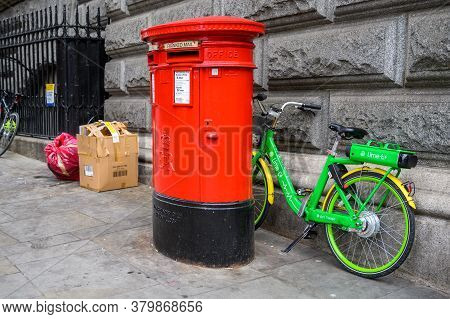 London - February 04, 2020: A Lime Electric Assist Rental Bike Parked Between A Wall And A Tradition