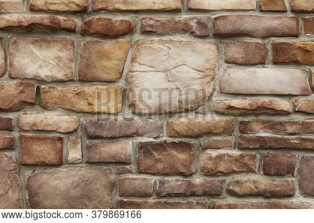 Old Odd Shaped Tan And Brown Thick Cut Stone Block Wall With Grout Shadows And Straight Lines Suitab