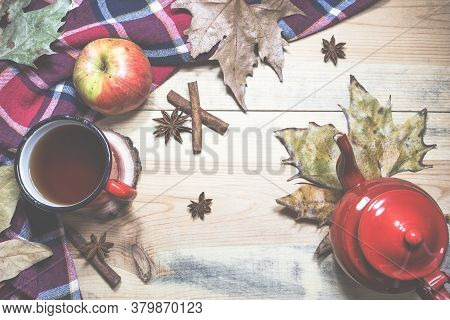 Hot Tea, Warm Blanket, Apple, Cinnamon Sticks, Anise Star And Autumn Leaves On Old Wooden Background
