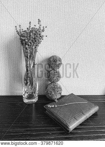 A Glass Vase With Lavender And Decorative Balls Favorably Emphasizes The Leather Surface Of The Diar