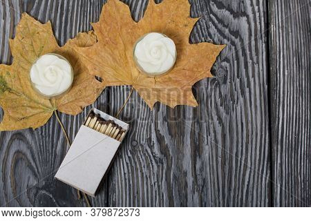 Two Decorative Candles In The Shape Of A Flower. Next To Them Are A Box Of Matches And Dried Maple L