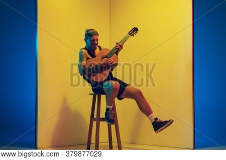 Young Musician With Guitar Performing On Yellow Background In Neon Light. Concept Of Music, Hobby, F