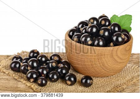 Black Currant In The Bowl On Wooden Table Isolated On White Background With Clipping Path And Full D