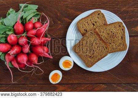 Slices Of Rye Bread On A White Plate With A Cut Boiled Egg And A Bunch Of Red Radishes On A Brown Wo