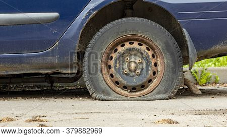 Flat Tire And Rusty Disc Of A Blue Car