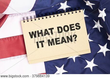 Notepad Isolated On The Background Of The American Flag. With The Text What Does It Mean