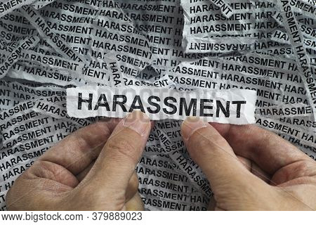 Harassment. Man Holding Torn Piece Of Paper With The Word Harassment In His Hands. Concept Image. Cl