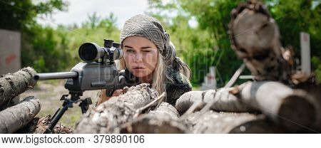 Female Soldier Shooting With Sniper Rifle. Woman With Weapon