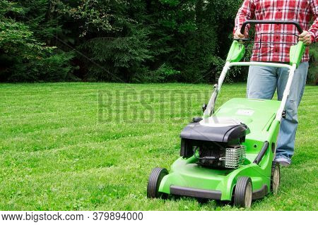 A Man Mowing The Lawn. Cutting Grass. Man Working On A Backyard. Man Cutting Grass In The Garden Wit