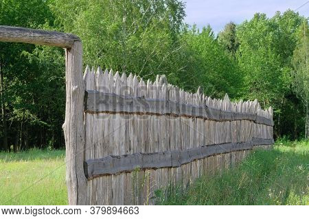 Wooden Rustic Fence In Village Near The Forest. Authentic Traditional Culture In Architecture And Li