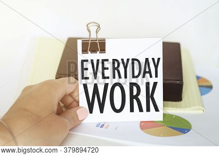 Woman S Hand Holds A Piece Of Paper With Text Everyday Work On The Background Of Graphs And Notepad