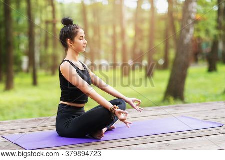 Female Trainer In Sportswear, Practicing Yoga Asanas, Performs The Lotus Exercise In The Park On A W