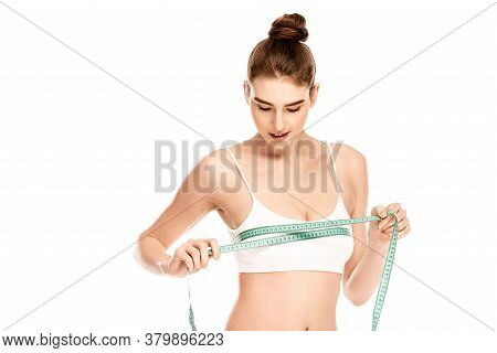 Model In Top Holding Measuring Tape While Measuring Bust Isolated On White Background