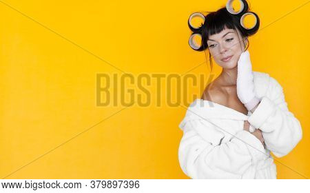 Young Beautiful Woman Housewife In A White Robe. Curlers On The Head. Yellow Background. Glove-shape