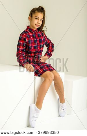 Beautiful Little Girl Poses For A Magazine In The Studio On A White Cube. Isolated On A White Backgr
