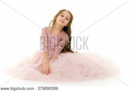 Lovely Blonde Girl Wearing Stylish Tulle Dress Sitting On The Floor On Her Knees Against White Backg