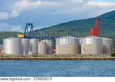 Industrial Fuel Tanks In The Seaport Against The Backdrop Of Mountains Covered With Green Forest