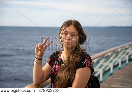 Photo Of A Young Preteen Girl With Long Brown Hair Makes A V-sign Towards The Camera. Blue Ocean And