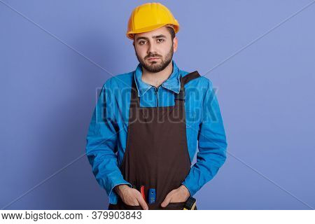 Serious Man Does Redecoration At Home, Wears Protective Helmet And Brown Apron, Poses Indoor Against
