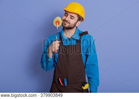 Decorator With Paint Roller In Hands Touching His Beard And Keeps Eyes Closed, Guy Wearing Helmet An
