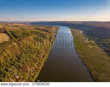 Flight Over The River And Small Village In Autumn. Moldova Republic Of. Molovata Village. River Dnie