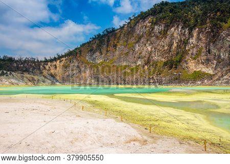 The Yellow Sulphur Deposits And Blue Lake Of Kawah Putih, Java, Indonesia