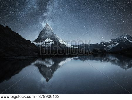 Swiss Landscape. Matterhorn And Reflection On The Water Surface At The Night Time. Milky Way Above M