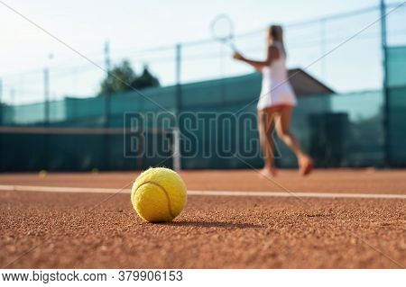 Healthy Lifectyle. A Young Girl Plays Tennis On The Court. The View On The Ball And A Tennis Player.