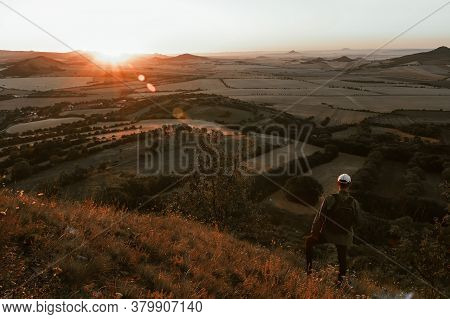 Young Man With Backpack Walking Down From Hill And Looking To Czech Ore Mountain Valley At Sunrise.