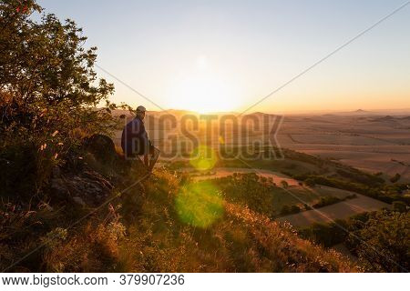 Young Man With Backpack Sitting On Hill And Looking To Czech Ore Mountain Valley At Sunrise. Czech L