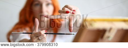 Close-up Of Female Hands Choosing Proportions For Painting. Red Haired Painter Holding Working Equip