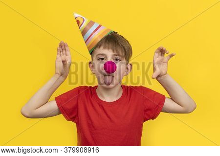 Child With Red Clown Nose On Yellow Background. Cheerful Clown Boy. 1 April Fools Day Concept