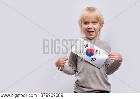 Fair-haired Boy With Sly Face Holding Flag Of South Korea On White Background