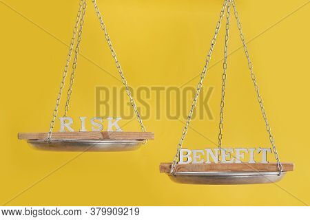Risk Vs Benefit In Balance. Concept Of Equilibrium. Balance Scales On Yellow Background Close Up.