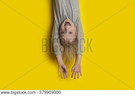 Surprised Fair-haired Boy Hanging Upside Down With Arms Outstretched. Portrait Of Child On Bright Ye