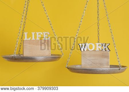 Work And Life Balance Concept. Balance Scales On Yellow Background Close Up.