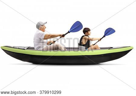 Profile shot of an elderly woman and a boy paddling in a canoe isolated on white background