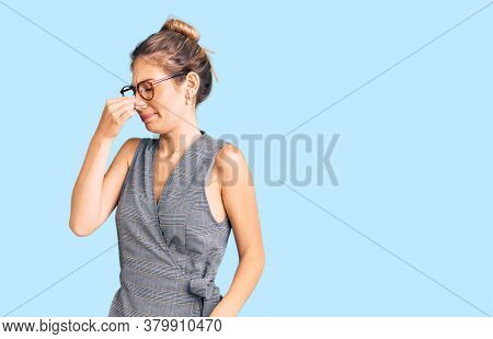 Beautiful caucasian woman with blonde hair wearing business clothes and glasses smelling something stinky and disgusting, intolerable smell, holding breath with fingers on nose. bad smell
