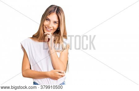 Beautiful caucasian woman with blonde hair wearing casual white tshirt looking confident at the camera with smile with crossed arms and hand raised on chin. thinking positive.