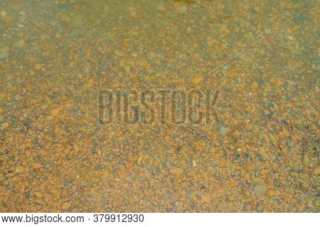 Many Smooth Stones On Yellow Sandy Bottom Of Mountain River. Nature Background Of Yellow Clay Bottom